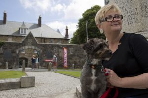 Spingo our museum dog and Mary the museum director sitting on the war memorial with the museum in the background