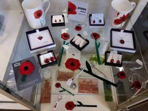 Various items with a poppy theme, mainly made of glass arranged on a display shelf