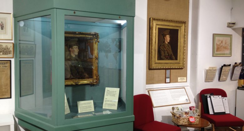 A museum display case displaying paintings of a world war 1 soldier by the artsit Stanhope Forbes