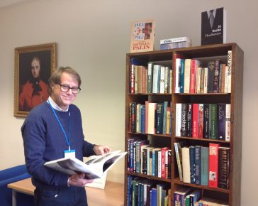Second hand bookshelves in the museum with volunteer David Whitehead looking at a book