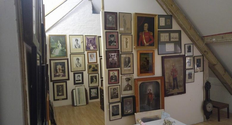 A light attic room with old pictures, portraits and photographs of various sizes, shapes and colours hanging from floor to ceiling