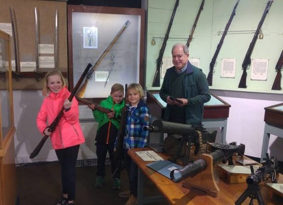 A group of children posing with historic firearms