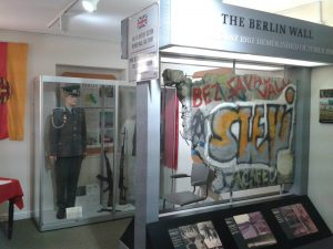 A view of a museum display showing a large section of the Berlin wall, heavy with graffiti