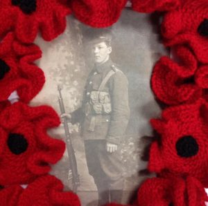 A sepia image of a private of the Great War surrounded by bight red knitted poppies