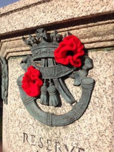The DCLI insignia on the Museum's memorial decorated with bright red knitted poppies