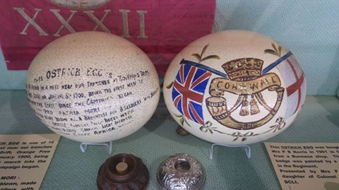 Two colourful and highly decorated hand-painted Ostrich eggs sit in a display case surrounded by smaller artefacts. The eggs on the right has the DCLI insignia and the egg on the left is decorated in handwritten script