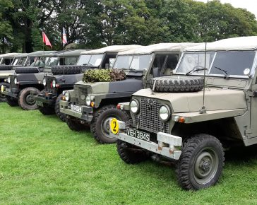 A row of Military vehicles lined up on grass