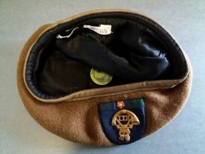 A Light Infantry beret lies upside down, showing the hand sewn accession label inside