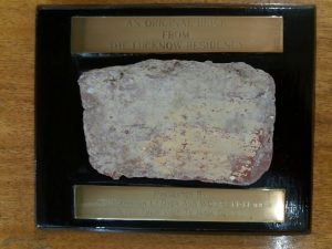 A small and deteriorated brick mounted on a wooden base, with an unreadable brass plaque