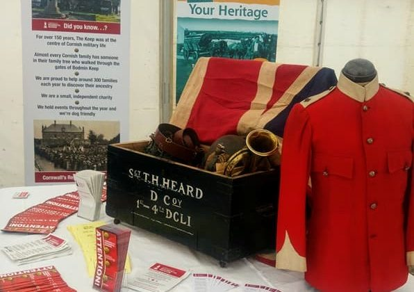 Cornwalls Regimental Museum on the Road! A display of items (including a flag, red military jacket and a bugle) arranged in a wooden chest, surrounded by leaflets, in a white marquee.