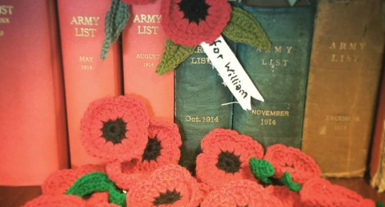 Twenty bright red handmade Poppies for Cornwall's Regimental Museum arranged against some WW1 era books in the library