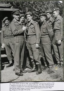 Frank Gillard, BBC, interviewing members of 5/DCLI. The Wessex Wyvern insignia is visible on their uniforms.