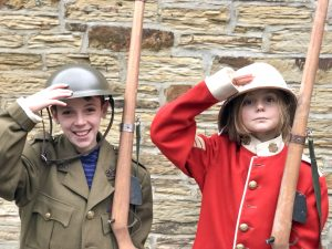 Kids dressed up in military uniforms, saluting