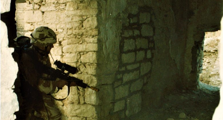 Photograph of soldier with their gun at the ready, entering a ruined building.