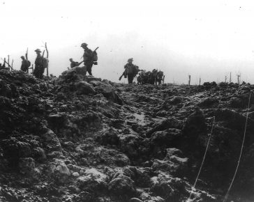 Soldiers march through a shelled battlefield.