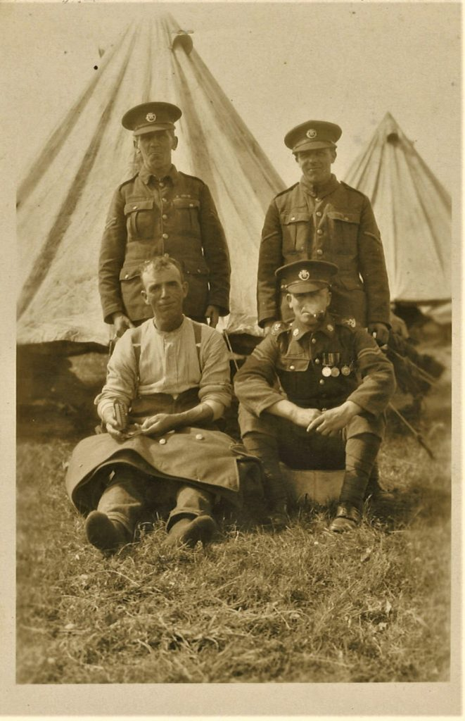 Photo of 4 non-commissioned officers – the man sitting on the left is using a sewing kit to fix the jacket which is lying across his lap