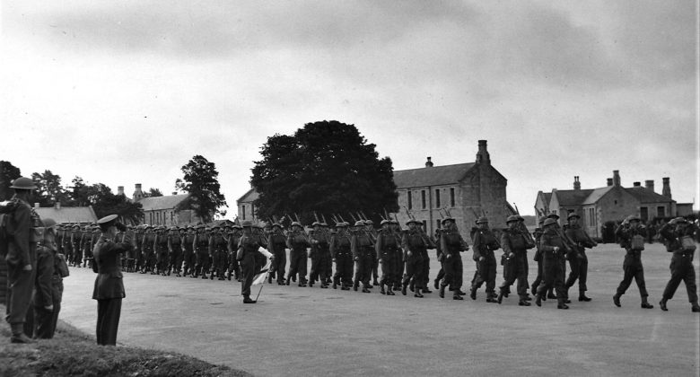 Black and white photograph of troops marching in a line outside Bodmin Barracks.