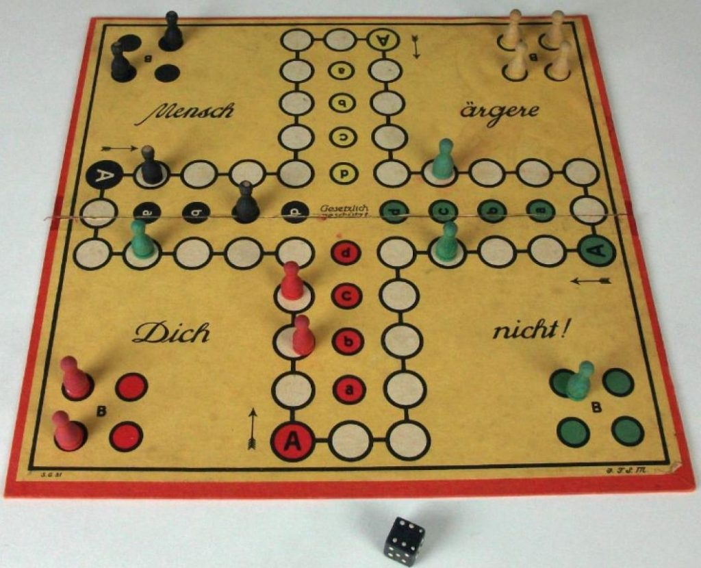 German Board game called 'Don't Get Annoyed With Me'. Markers of four different colours are positioned at different points on the board. A six sided black dice lies below the board.
