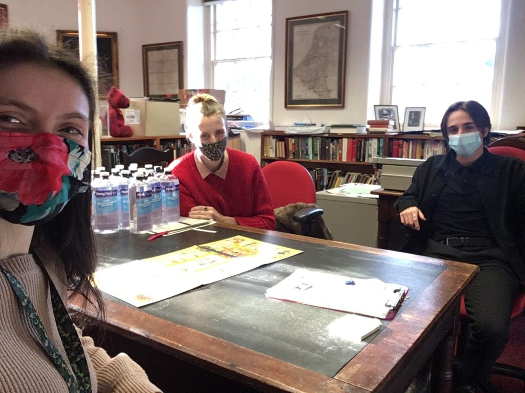 Two women and a man wearing covid-19 masks, distanced around a table. On top of the table lies a board game.